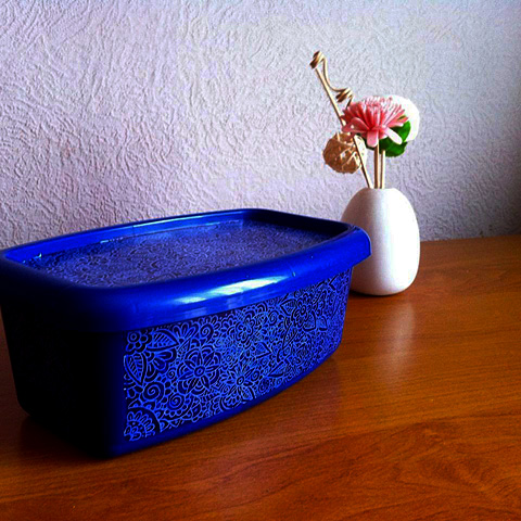 Recycle old plastic container. Paint over the labels with acrylic paints and draw floral doodles with a paint marker.
